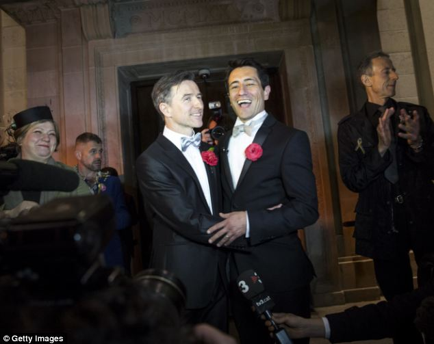 Earlybirds: Peter McGraith (left) and David Cabreza embraced each other outside Islington Town Hall in the early hours of this morning after their wedding on the stroke of midnight