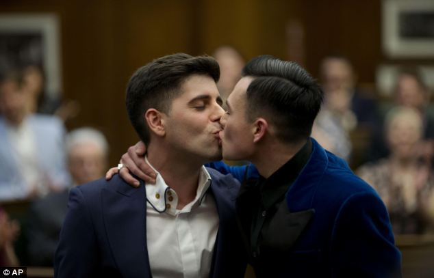 Sean Adl-Tabatabai, left, and Sinclair Treadway kiss each other after they were announced officially married during a wedding ceremony in the Council Chamber at Camden Town Hall in London, minutes into Saturday