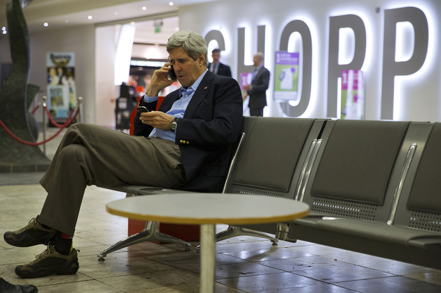 U.S. Secretary of State John Kerry speaks on his cell phone at Shannon Airport in Ireland, Saturday March 29, 2014, during a refueling stop. Halfway home fro...