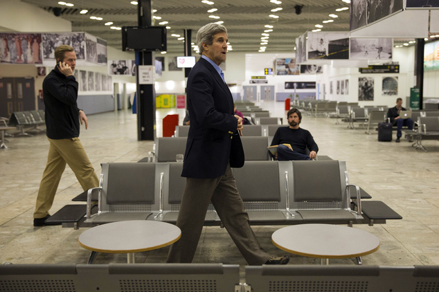 U.S. Secretary of State John Kerry walks back to his plane through Shannon Airport in Ireland Saturday March 29, 2014, during a refueling stop. Halfway home ...