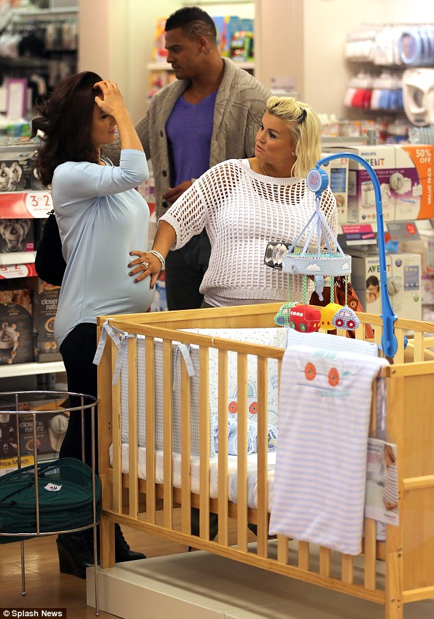 Feel that: Kerry was seen placing her hand on Rosanna's bump again in the Mothercare store, while her former rugby player fiance shopped away behind her