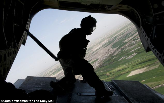 From the top: A soldier looks out from a British helicopter. Lt Col Slack, said that he will not be able to sleep properly until the last one of his soldiers is off the ground and 'back home safely'