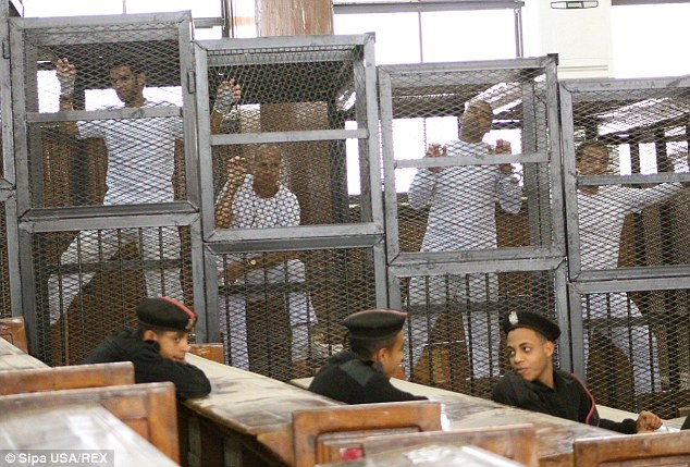 Paraded: Defendants in the cages of the Cairo courtroom at a previous hearing. Defendants include (left to right) Student Suhaib Saeed, and Al-Jazeera journalists Peter Greste, Mohamed Fahmy and Baher Modhamed