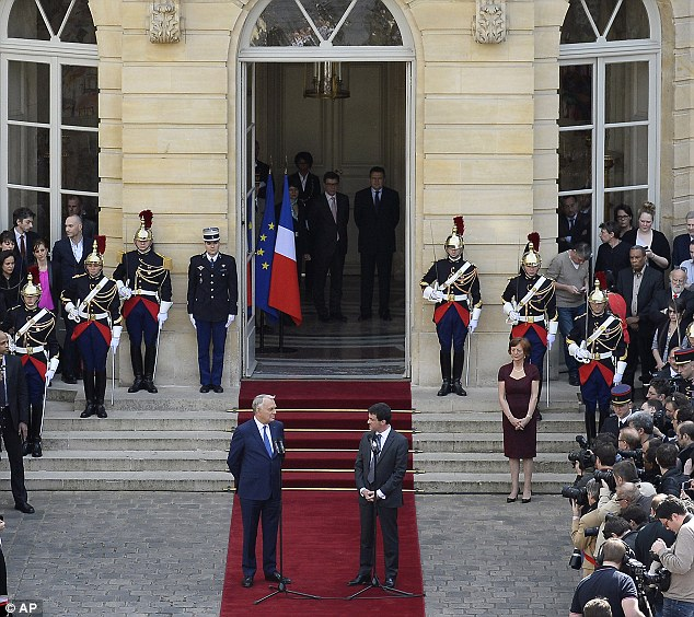 Outgoing French Prime Minister Jean-Marc Ayrault, left, looks at new French Prime Minister Manuel Valls, right on the carpet, after the takeover ceremony at the Prime Ministry in Paris