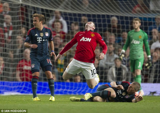 Down he goes: Schweinsteiger fouls Rooney and the United man hits the deck
