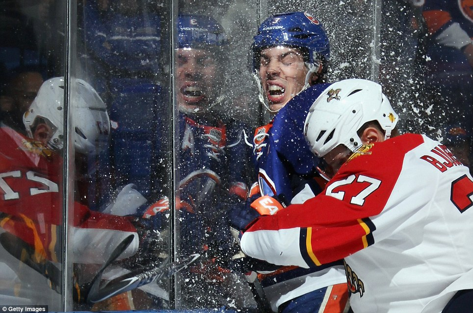 Travis Hamonic of the New York Islanders is hit into the glass by Nick Bjugstad of the Florida Panthers during the first period