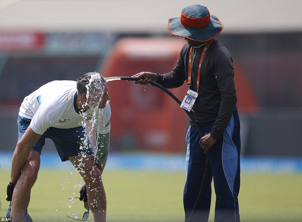A groundsman sprays water on South Africa's Dale Steyn during a training session ahead of their ICC Twenty20 Cricket World Cup semi-final match against India