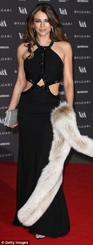 Dressed to impress: The actress looked typically amazing in a dramatic black gown with a cut-out middle, while accessorising with a fur stole and a glittering silver clutch bag