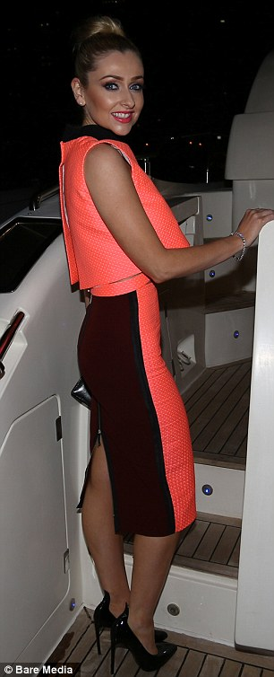Dressed to impress: Featuring a daring cutaway panel, the 29-year-old TV star's vibrant top was teamed with a matching high-waisted pencil skirt and black patent skyscraper heels, which she dutifully removed when she climbed on board the yacht