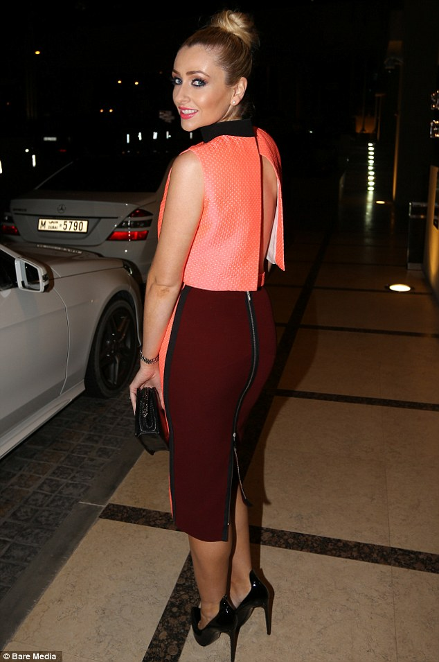 Pert posterior: Turning around to flash her pert posterior towards the camera as she wandered aboard, Gemma displayed the striking backless detail of her top and a corresponding berry-coloured zip-back to her ladylike pencil skirt