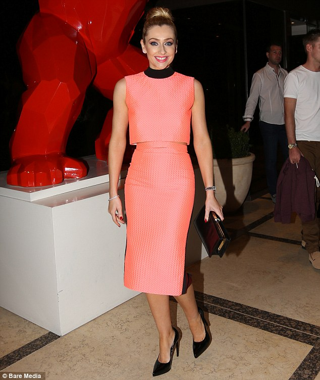 Pretty in pink: The bubbly blonde completed her party look with a simple black clutch bag and wore her hair swept up into a stylish top-knot, while injecting a further pop of colour with a slick of red lipgloss