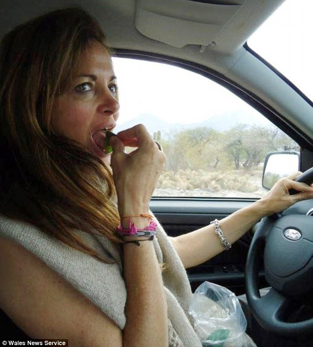 On the road: In this picture, shown to the jury, a cactus can be seen in the background as Johnson eats at the wheel of a left-hand-drive car