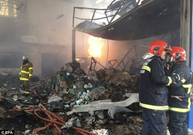 Thai firemen stand amid smouldering rubble after an explosion blew up a scrap metal warehouse in northern Bangkok