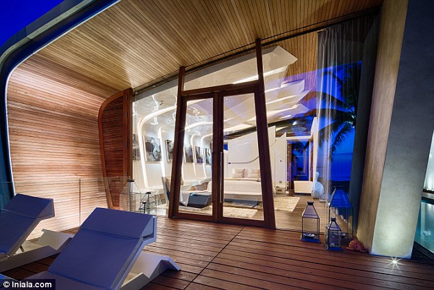 Gorgeous at night: The glass walled palatial rental reflects the ocean in the evening