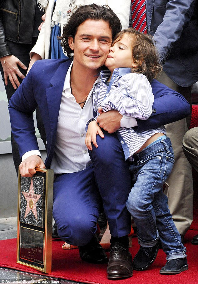 Getting bored? Orlando Bloom tries to keep Flynn entertained while posing for the world's media
