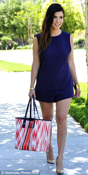 All mine: Kourtney rounded off her ensemble with a multicolored handbag embossed with her initials