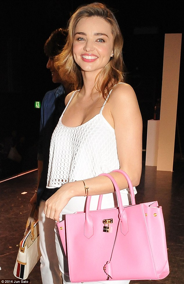 Chic and sleek: On stage, the former Victoria's Secret Angel sported a crisp white pencil skirt along with a white eyelet crop top, while carrying a sleek bubble gum pink purse