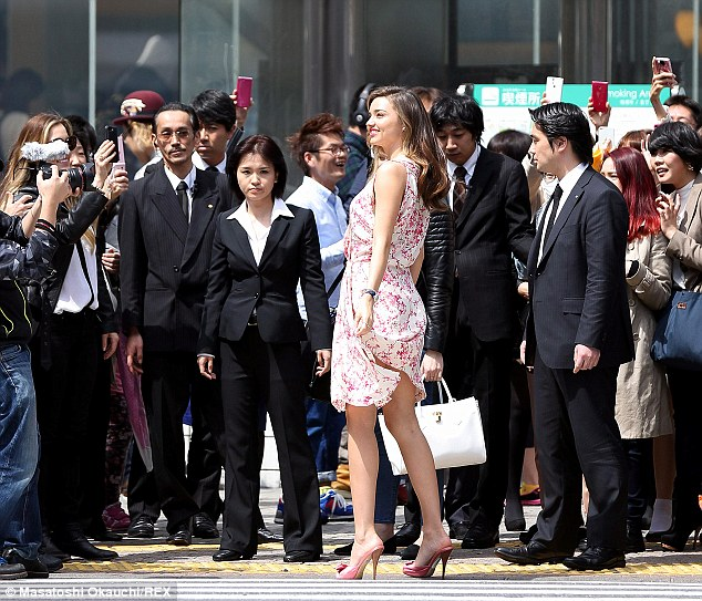 All eyes on me: Assistants for a loose gauntlet around Miranda as fans gather for a photo of the Australian model