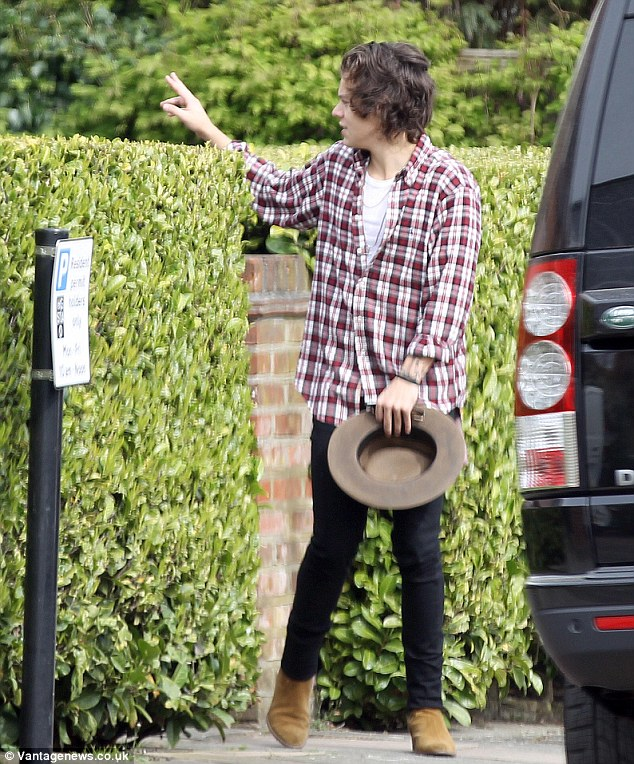 Harry heads off after his test drive of the Porsche giving a peace sign