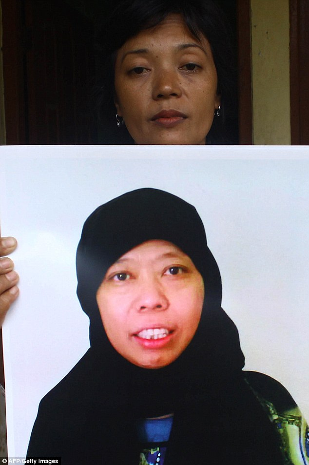 Freed by the Indonesian government: Satinah Binti Jumadi Ahmad's sister in law holds up her picture of the Indonesian maid who was found guilty of murder in Saudi Arabia