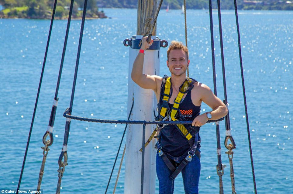 Exciting times: During his time in Australia Andrew has also slid down a 91-meter-long typhoon waterslide. He is pictured claiming a tall ship's mast