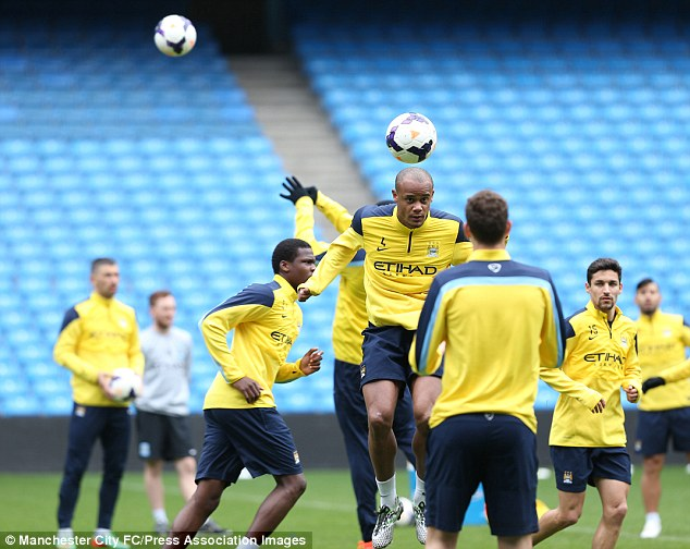 Up for it: City captain Vincent Kompany (top) warms up with his teammates during training on Friday