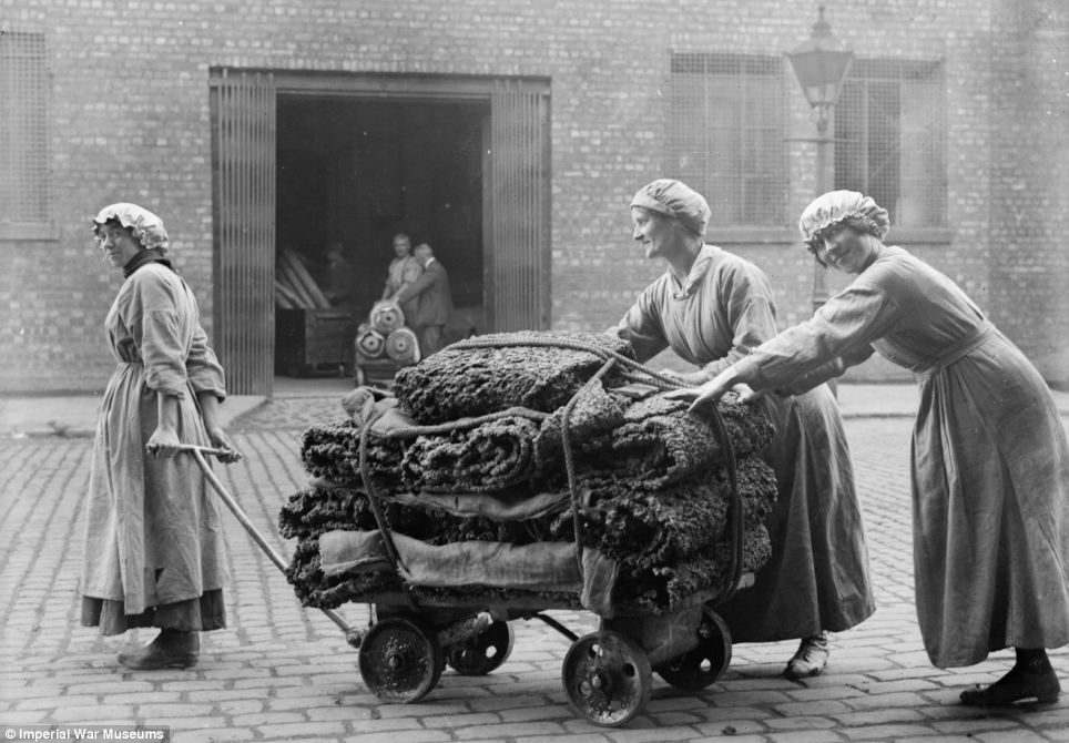 Female workers tow a trolley of raw rubber from a warehouse at the factory of Charles Macintosh and Sons Ltd in Manchester in September 1918
