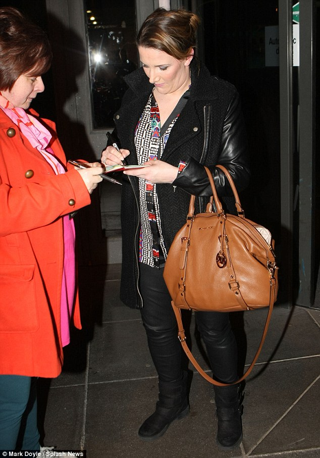 Here you go: The X Factor winner signs autographs as she makes her way out onto the street