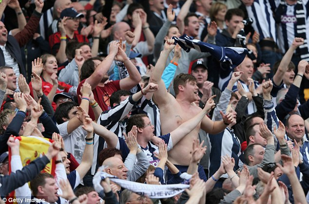 Victory dance: West Brom fans sing their team's praises at the end of the match in Norwich