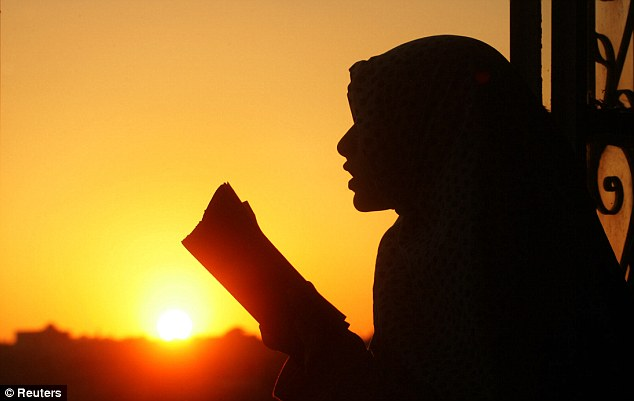 Fast: A girl reads from the Koran on the last Friday of the Islamic holy month of Ramadan (file photo). Muslims across the world abstain from eating and drinking from sunrise to sunset during the period