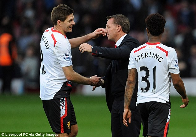 On top of the pile: Brendan Rodgers and Steven Gerrard embrace after a determined victory - their seventh in succession - at West Ham