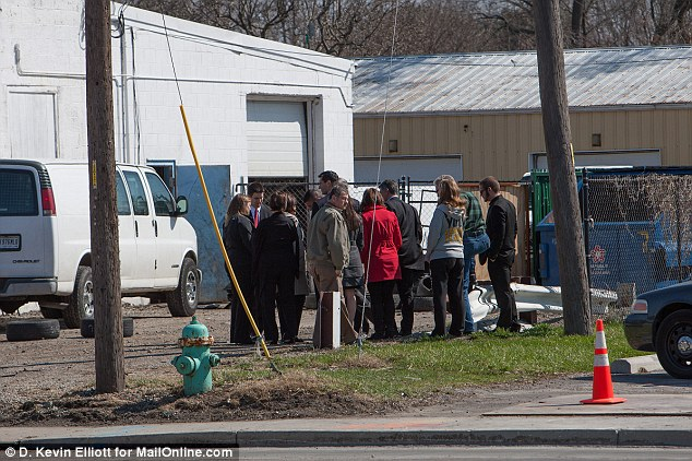 Left behind: Family and friends of Trapuzzano gather outside the tire shop on April 5