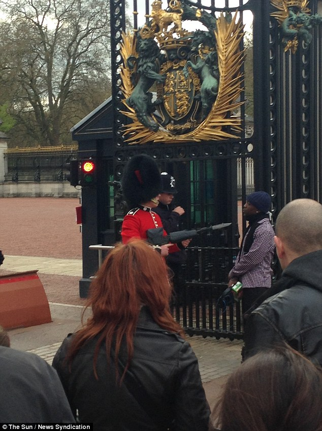 Tense encounter: A member of the Queen's Guard can be seen levelling his rifle, tipped with a bayonet, at the throat of a man in front of the gates of Buckingham Palace