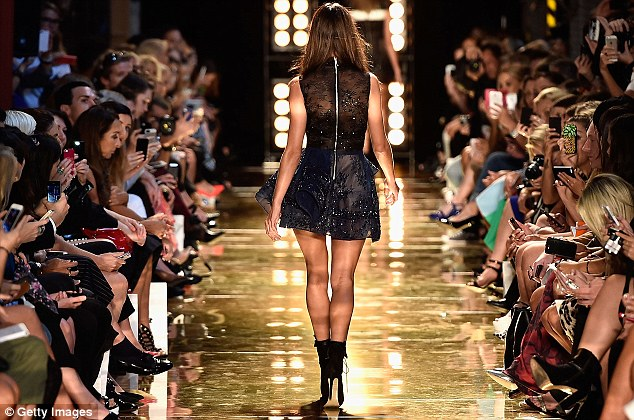 A different perspective: The model's incredible legs were on full display as she strutted in boots on her way back up the runway