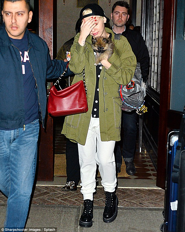 Laid back: The star wore a pair of white jogging bottoms with a khaki jacket
