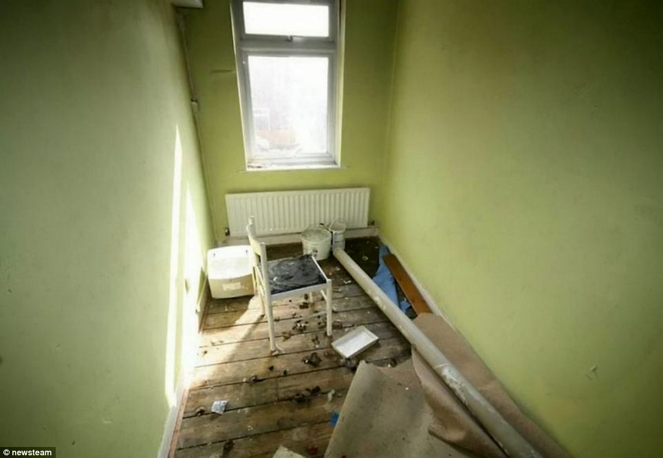 Another of the rooms in the property - with old carpets and broken furniture scattered across it. The home does come with a brick outbuilding and rear yard, however