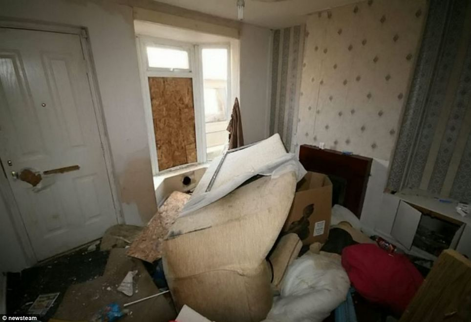 The front-facing living room of the terraced house - which comes complete with boarded-up windows, an upturned sofa and piles of rubbish