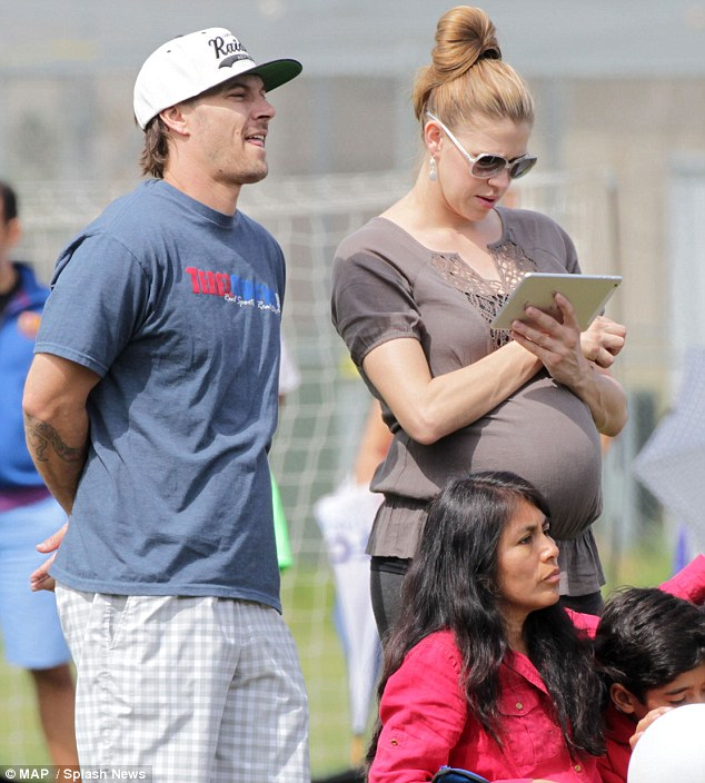 Pregnant and happy: The couple on March 23 in LA while watching Sean kick a soccer ball around