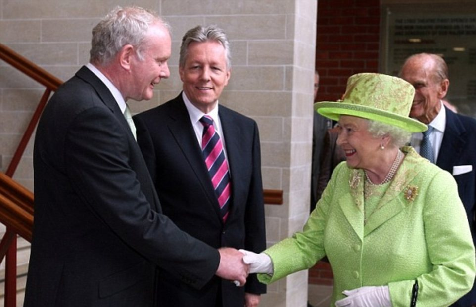 Historic moment: The Queen shakes hands with former IRA commander Martin McGuinness in front of Northern Ireland First Minister Peter Robinson (centre) and the world's cameras