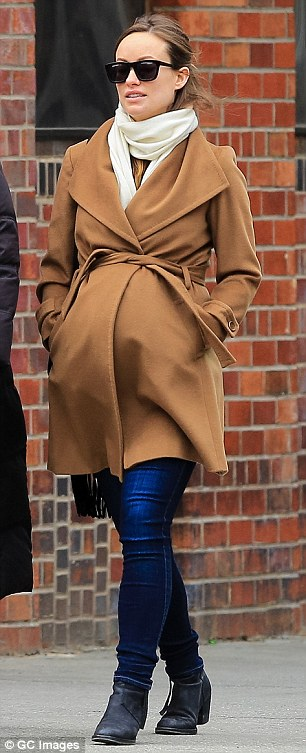 Maternity chic: Olivia Wilde dressed her very pregnant belly in a camel coat as she strolled around NYC on Monday