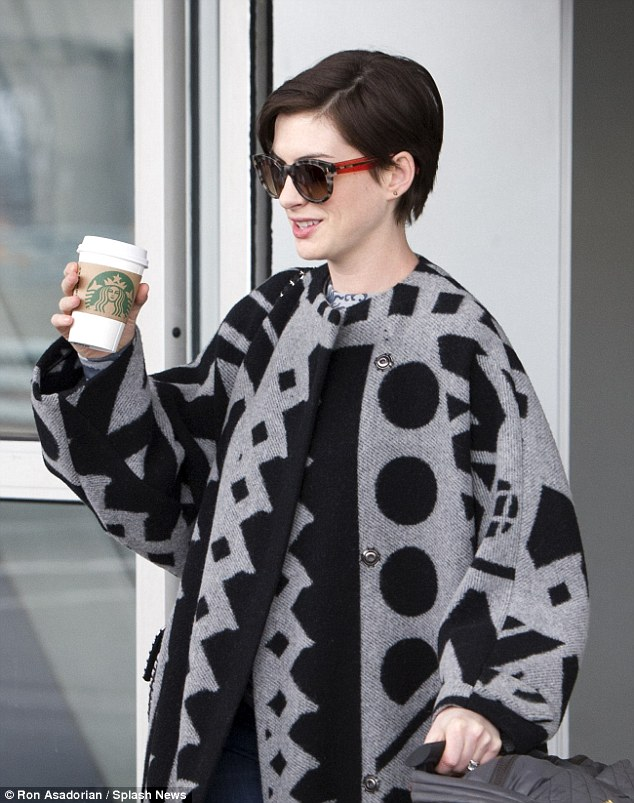 Caffeine fix: The jet-lagged actress - clutching her trusty cup of Starbucks - covered her make-up free face with tortoiseshell shades