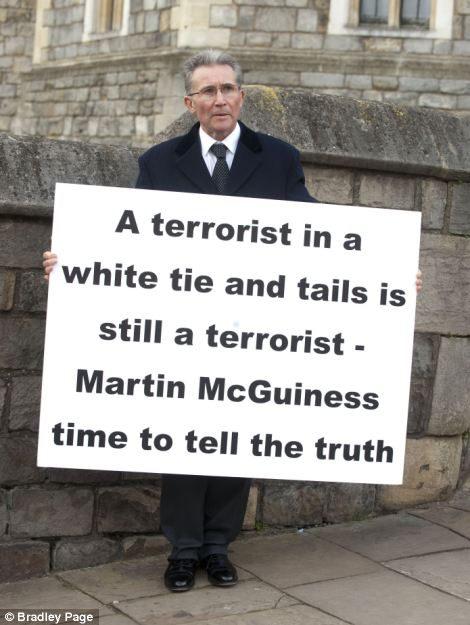 Protest: Victor Barker holds a hard-hitting sign bearing a message to dignitaries inside Windsor Castle. His son James was killed in the Omagh bombings carried out by the IRA in August 1998