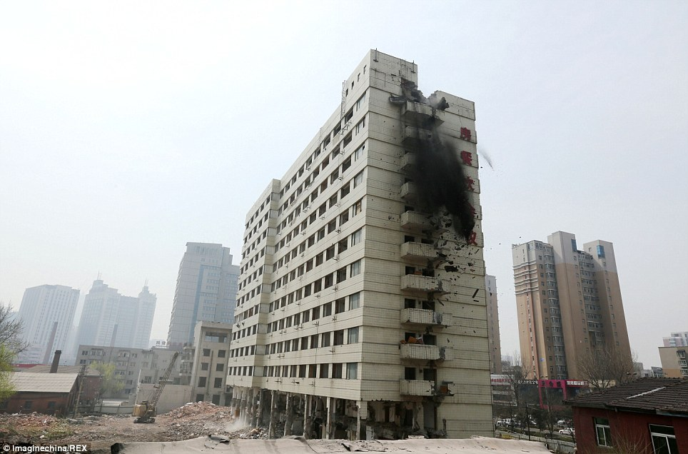 Falling apart: This photograph was taken just fractions of a second after demolition workers detonated the explosives. The Xiangyun Building is being demolished as Shenyan city officials consider its design and facilities dated