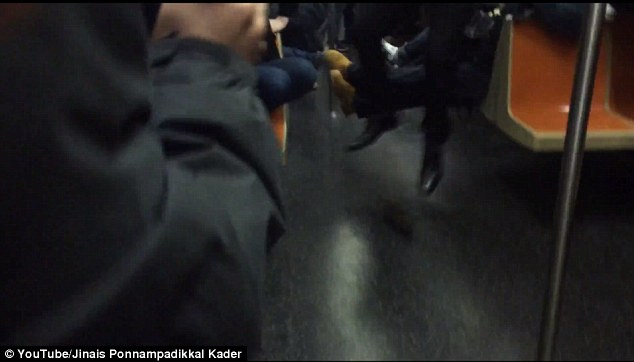Scared to death: One well-dressed commuter jumped in fear as the hideous rodent raced past his feet