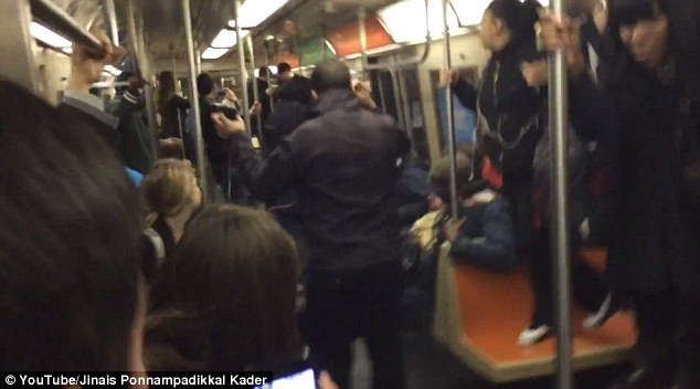 Alarmed: Footage shows dozens of trapped commuters standing on seats to avoid the giant rat