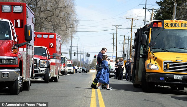 Rescue operation: A young student is taken to a school bus during the decontamination process