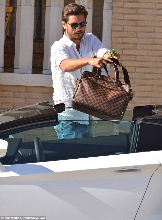 Get in there, son: After throwing his designer bag into the back of his car, the socialite opened up the butterfly doors