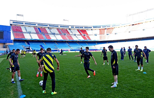 Going through the motions: The Barcelona players get to grips with the uncut grass at Atletico Madrid's ground