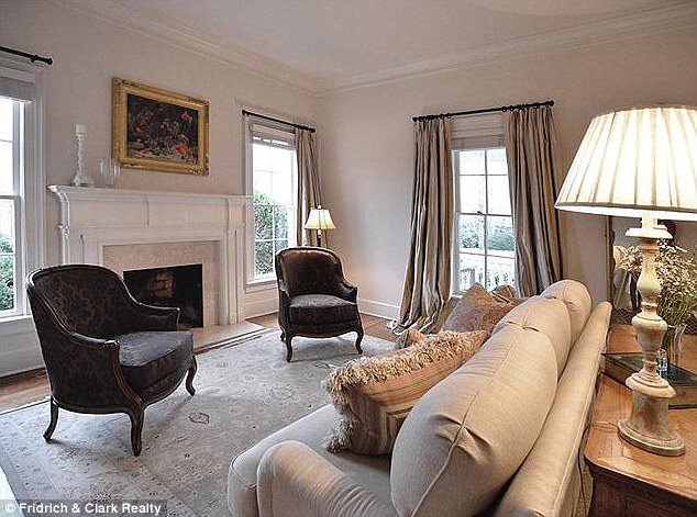 Cozy: The living room is decorated in a neutral pale grey, with simple furnishings and a marble fireplace