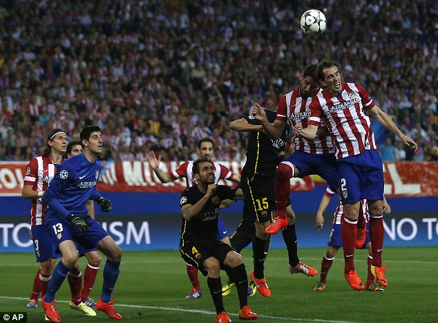 High jump: Atletico's Diego Godin jumps for the ball with team-mate Adrian Lopez